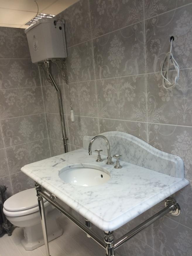 Marble sink. Patterned tiles. Higt flush toilet.
